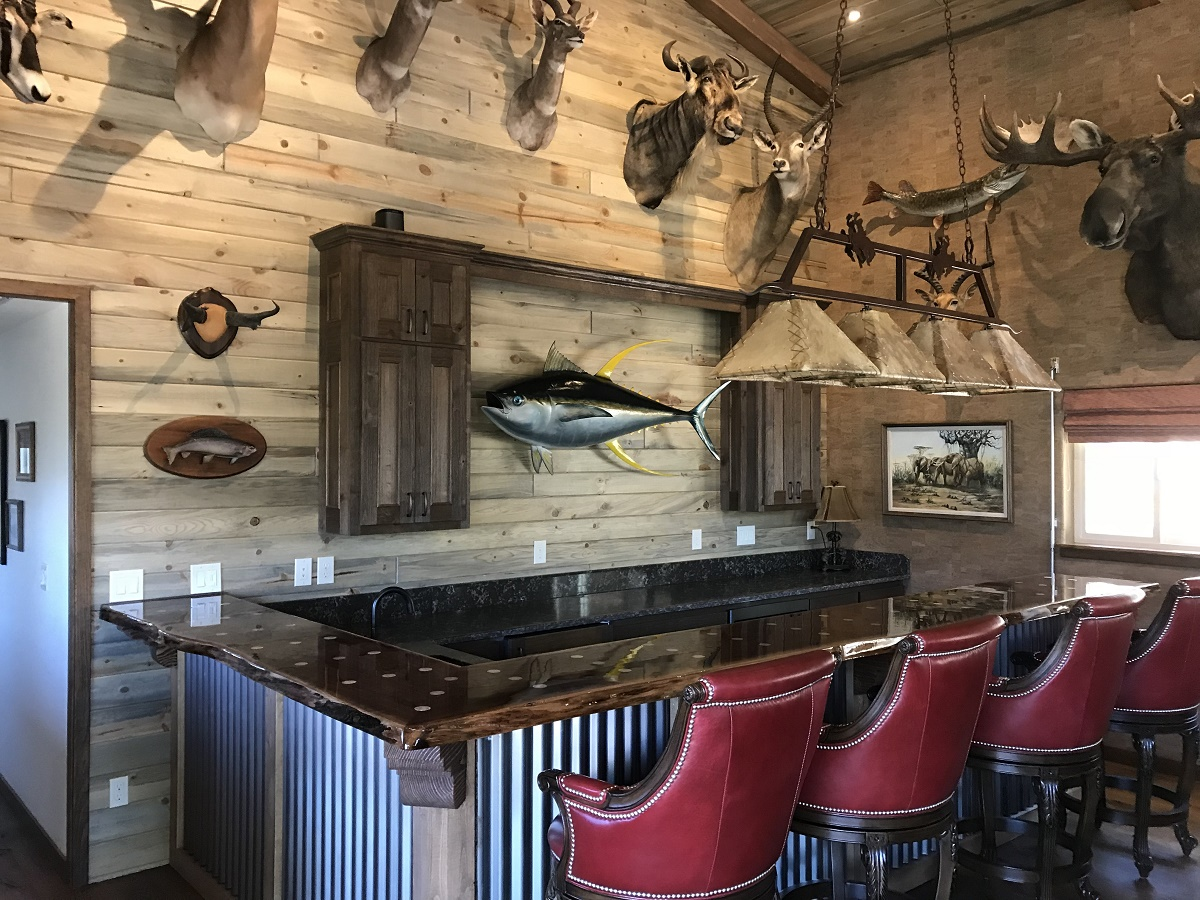 The custom bar complete with a wood slab top and inlaid silver dollars. Corrugated metal and wood beams make up the face.